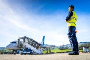 Ein Security-Mitarbeiter des Airports St. Gallen-Altenrhein überwacht das Vorfeld während die Embraer 170 der People's Vienna Line auf ihren nächsten Flug in Richtung Wien wartet.